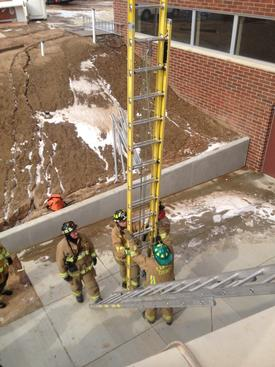 Crew set-up ladders to assist in the evacuation of the patient from the roof area